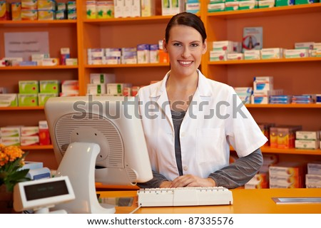 Happy pharmacist standing at checkout counter in a drugstore - stock photo