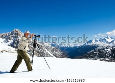 Happy photographer in snow mountains - stock photo