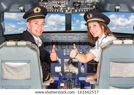 Happy Pilots in the Cockpit with Thumbs Up - stock photo