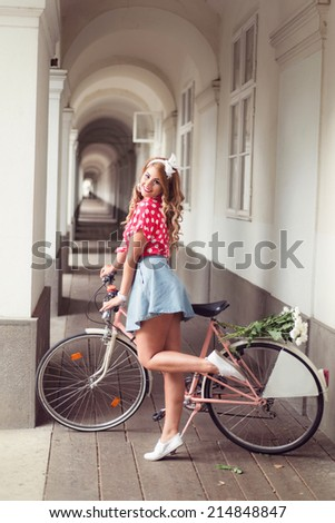 Happy Pin Up Girl posing next to her old retro bicycle, bike, dressed in a very short and sexy denim skirt and red shirt with polka dots.  - stock photo