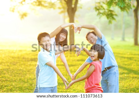 Happy playful Asian family forming love shape, outdoor green park - stock photo
