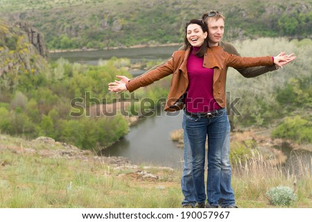 Happy playful attractive young couple rejoicing in the beauty of nature laughing as they stand with outstretched arms above a scenic valley with a wide river - stock photo