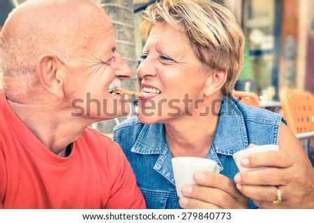 Happy playful senior couple in love tenderly enjoying a cup of coffee - Joyful elderly active lifestyle - Man having fun and smiling with her wife in bar cafe restaurant during evergreen vacation - stock photo