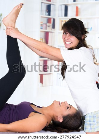 happy playful young woman lying while getting an leg massage from specialist concept of physiotherapy - stock photo