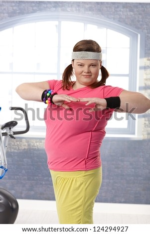 Happy plump woman exercising in colorful outfit at the gym. - stock photo
