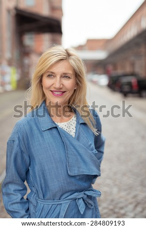 Happy Portrait of a Blond Woman, Wearing Fashionable Blue Dress, Standing at the Street and Looking Into Distance. - stock photo