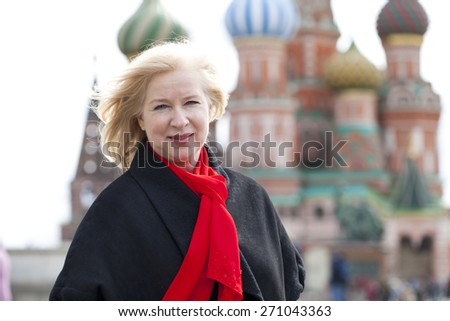 Happy portrait of an elderly blonde woman, against the background of the Red Square, Moscow, Russia - stock photo