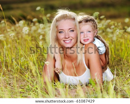 Happy portrait of the mother and little daughter outdoors - stock photo