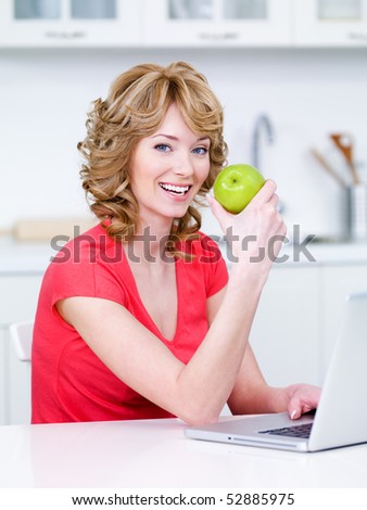 Happy portrait of young beautiful woman sitting in the kitchen and eating green apple - stock photo