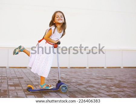 Happy positive child in dress on the scooter in the city - stock photo