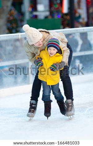 happy positive family of two ice skating at winter - stock photo