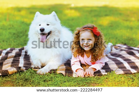 Happy positive little girl and dog having fun on the grass in warm sunny day - stock photo
