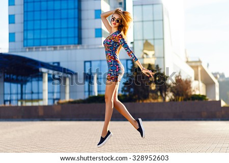 Happy positive summer portrait of cute sexy woman in bright mini dress jumping on the street, sunny day, urban style, make up, fashion accessorizes . - stock photo
