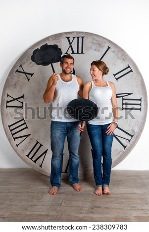 Happy Pregnant Couple dressed in white showing sign speech bubble banners looking happy excited and having idea on white background with giant clock - stock photo