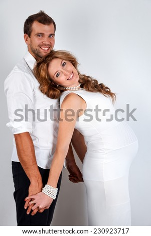 Happy Pregnant Couple on white background - stock photo