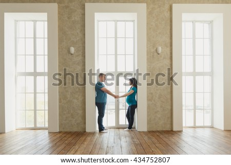 Happy pregnant couple standing near a window in a new house in a new housing. Mortgage and took happy or rented housing - stock photo