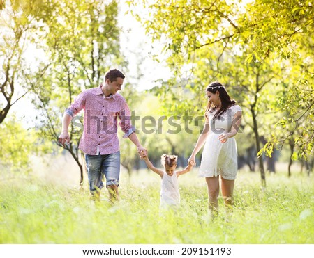 Happy pregnant family having fun in summer nature - stock photo