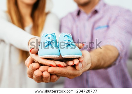 Happy pregnant parents holding colorful baby boots - stock photo