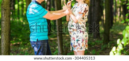 Happy pregnant woman and her husband in the park - stock photo