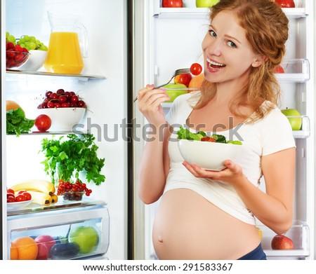 Happy pregnant woman eating salad near refrigerator at home - stock photo