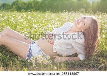 Happy pregnant woman is sitting in meadow of chamomile flowers, sunset time, new life concept - stock photo