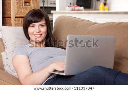 Happy pregnant woman looking at camera using laptop computer - stock photo