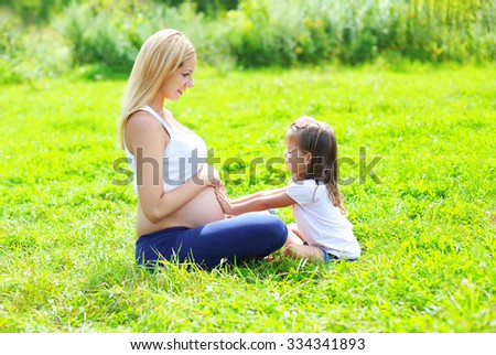 Happy pregnant woman, mother and little daughter child sitting on grass in summer day - stock photo