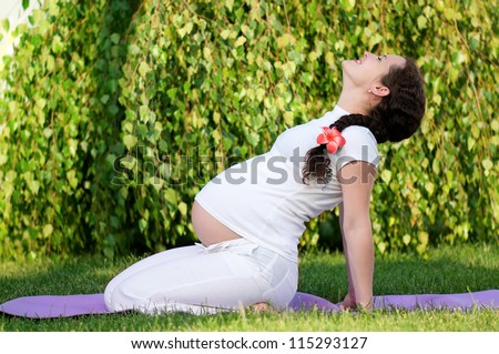 Happy pregnant woman relaxing in the park outdoors - stock photo