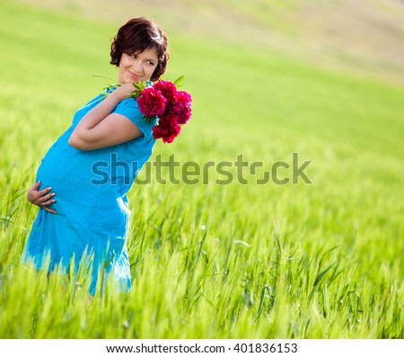 Happy pregnant woman with flowers outdoors, walking in field of green grass. - stock photo