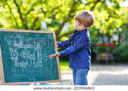 Happy preschool boy at blackboard making project presentation, outdoor school or nursery. - stock photo
