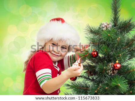 happy preschool girl decorating Christmas tree on green background - stock photo