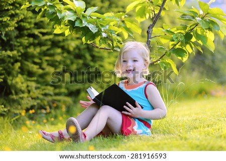 Happy preschooler child reading interesting book in the garden. Cute little girl relaxing and playing outdoors in the park enjoying sunny summer day. - stock photo