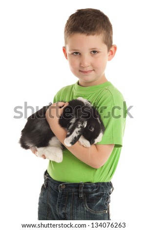 Happy preschooler with a domestic lop-eared rabbit. - stock photo
