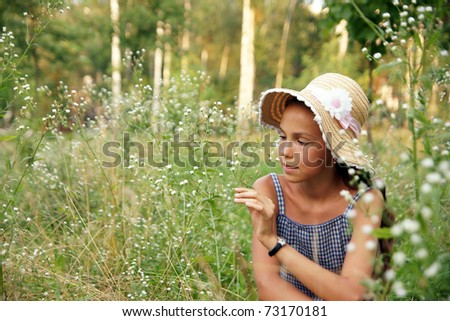 Happy preteen girl plays with flowers on meadow background - stock photo