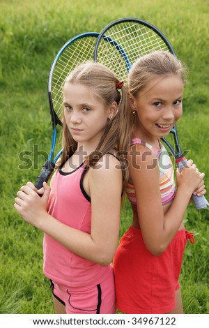 Happy preteen girls in sport outfits with tennis rackets on green grass background - stock photo