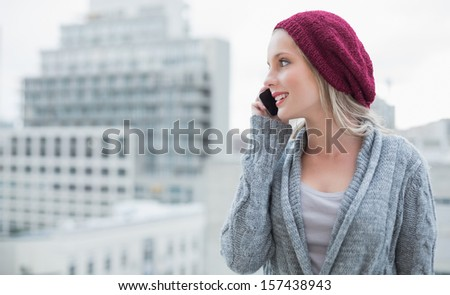 Happy pretty blonde on the phone outdoors on urban background - stock photo