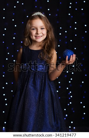 Happy pretty child girl is wearing fashion dress and crown holding blue Christmas tree ball in hands over background scene with lights, holiday concept - stock photo