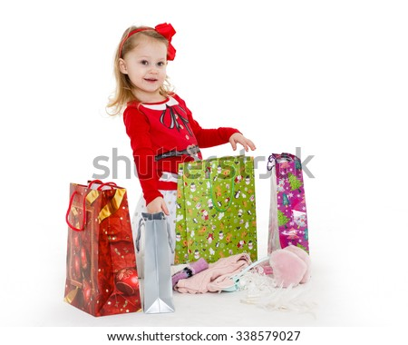 Happy pretty little child with shopping bags sits on a white background. 3 year old. - stock photo