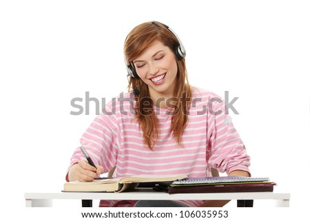 Happy pretty student girl is learning with headset, books and files. Young woman is writing and laughing.  Isolated on the white background. - stock photo