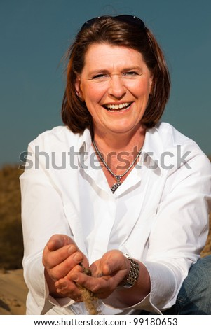 Happy pretty woman middle aged enjoying outdoors playing with sand. Clear sunny spring day with blue sky. - stock photo