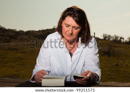 Happy pretty woman middle aged reading a book and enjoying outdoors. Clear sunny spring day with blue sky. - stock photo
