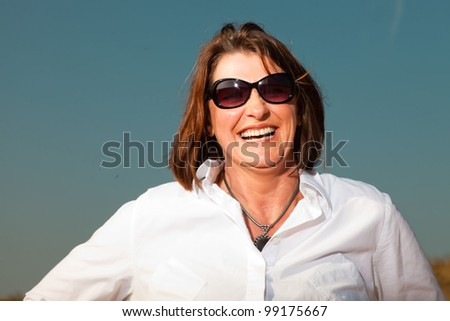 Happy pretty woman middle aged with sunglasses enjoying outdoors. Clear sunny spring day with blue sky. - stock photo