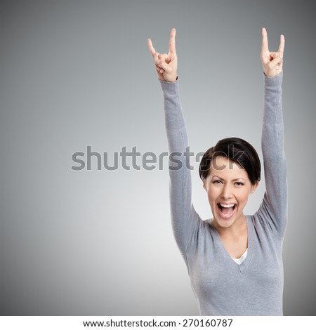 Happy pretty woman puts her hands up, isolated on grey - stock photo
