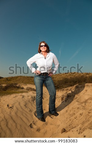Happy pretty woman with sunglasses middle aged enjoying outdoors. Feeling free standing in dune landscape. Clear sunny spring day with blue sky. - stock photo