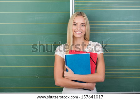 Happy pretty young female student with long blond her clutching her class notes in folders to her chest as she stands in front of the blackboard - stock photo