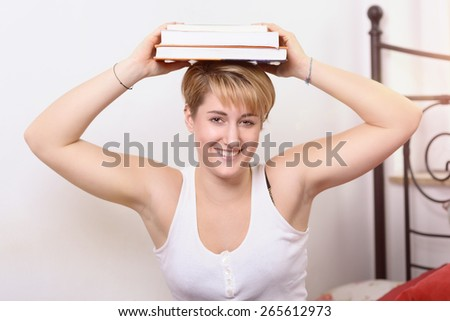 Happy pretty young woman taking a break from her college studies balancing books on her head as she looks at the camera with a warm friendly smile - stock photo