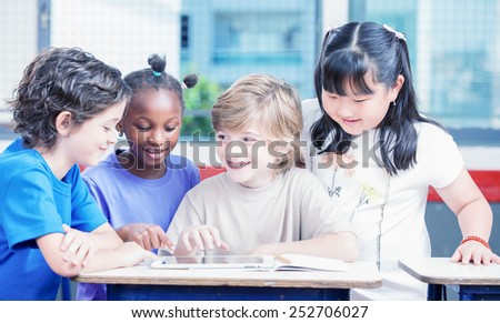 Happy primary multi ethnic students at desk with tablet and exercise book. - stock photo