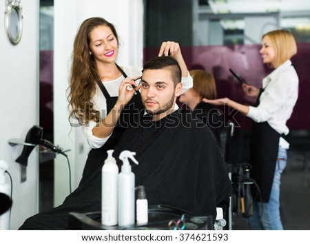 Happy professional young hairdresser doing hairstyle for young men - stock photo