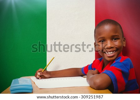 Happy pupil at desk against italy national flag - stock photo