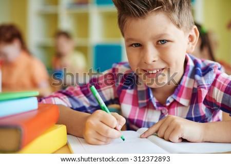 Happy pupil drawing and looking at camera at lesson - stock photo